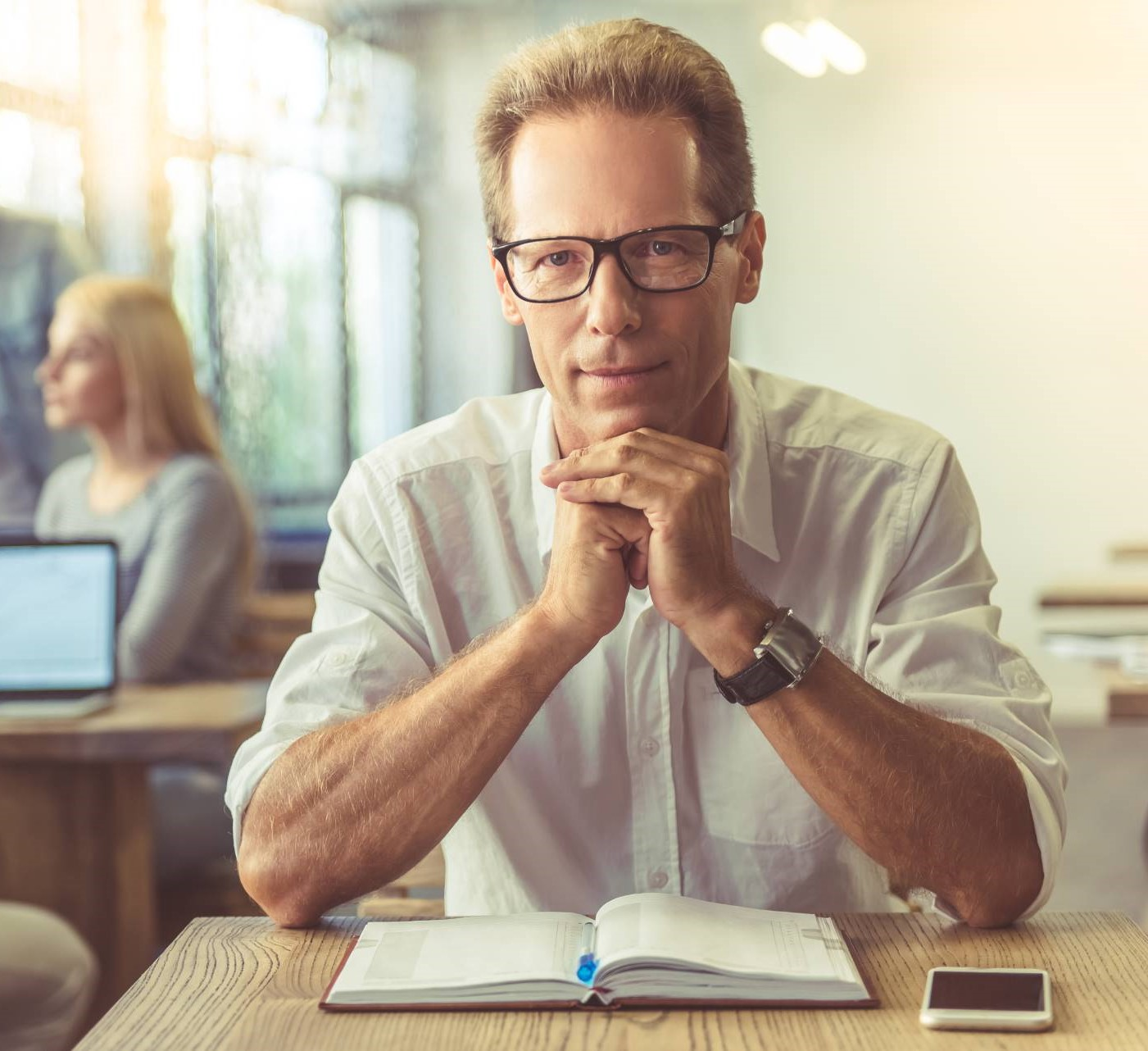 Businessman in shirt and eyeglasses is looking at camera.